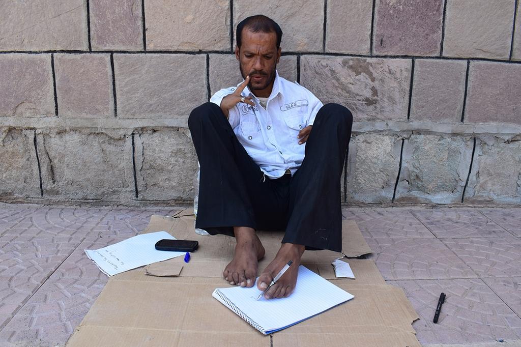 رجل يمني ولد بغير ذراعين ولديه القدرة على الكتابة بقدميه وتلبية احتياجاته ومواجهة واقعه في منطقة حرب (صور)